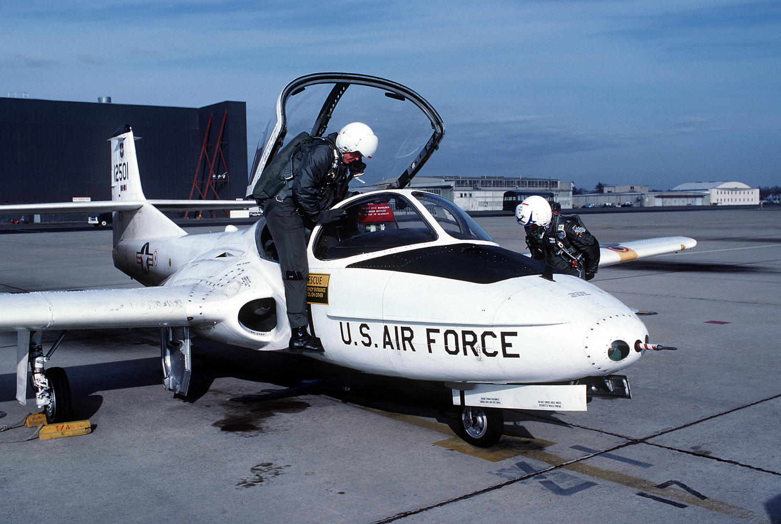 A student and instructor at the Air Training Command undergraduate navigator school climb into the cockpit of a T-37 training aircraft prior to making a flight