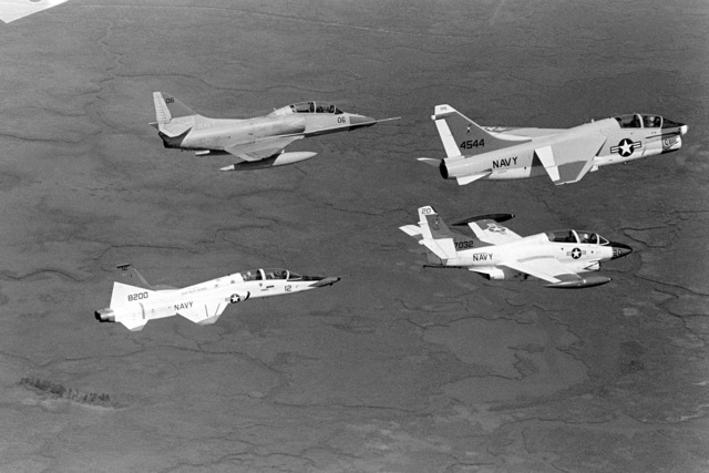 An air-to-air right side view of a TA-4 Skyhawk aircraft, top left, a TA-7 Corsair II aircraft, top right, a T-38 Talon aircraft, bottom left, and a T-2 Buckeye aircraft in flight near the Naval Air Test Center Patuxent River, Maryland