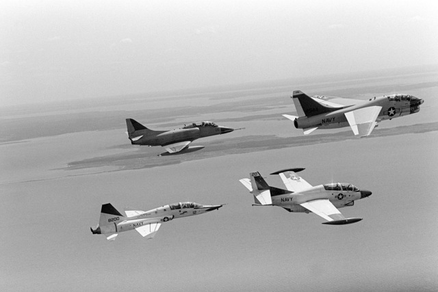 An air-to-air right side view of a TA-4 Skyhawk aircraft, top left, a TA-7 Corsair II aircraft, top right, a T-38 Talon aircraft, bottom left, and a T-2 Buckeye aircraft in flight near the Naval Air Test Center, Patuxent River, Maryland