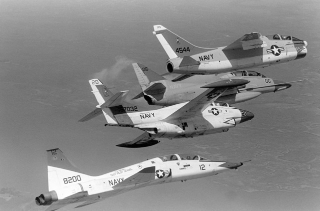 An air-to-air right side view of, from top to bottom, a TA-7 Corsair II aircraft, a TA-4 Skyhawk aircraft, a T-2 Buckeye aircraft and a T-38 Talon aircraft in flight near the Naval Air Test Center, Patuxent River, Maryland