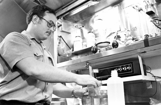 Boiler Technician 2nd Class Larry Owens conducts a test on a water sample taken from one of the boilers of the guided missile cruiser USS JOUETT (CG 29)