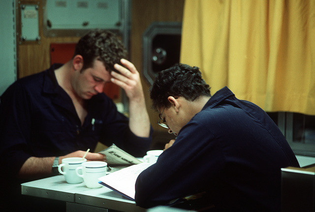 Crewmen studying in the mess deck are aboard the Los Angeles class nuclear-powered attack submarine USS LA JOLLA (SSN-701). Due to limited space the mess deck area also serves as a lounge and movie theater