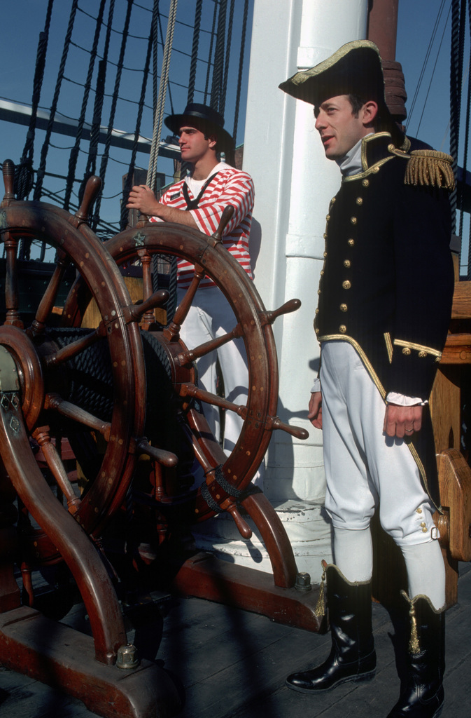 Lieutenant Shan Delmar, executive officer, stands on the spar deck of the sailing frigate USS CONSTITUTION wearing a War of 1812 lieutenant's uniform as guests tour the ship. PHOTO from June 1983 All Hands Magazine