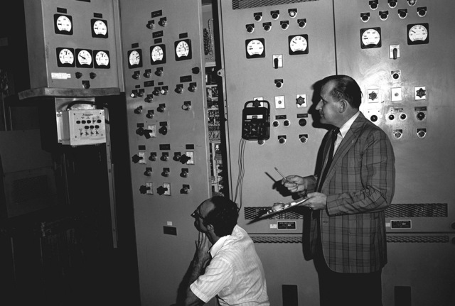 Ray Unger, kneeling, and John Tichy check automatic synchronizers on the motor generator panel of the uninterrupted power system (UPS). UPS provides guaranteed electrical power to critical systems at defense installations