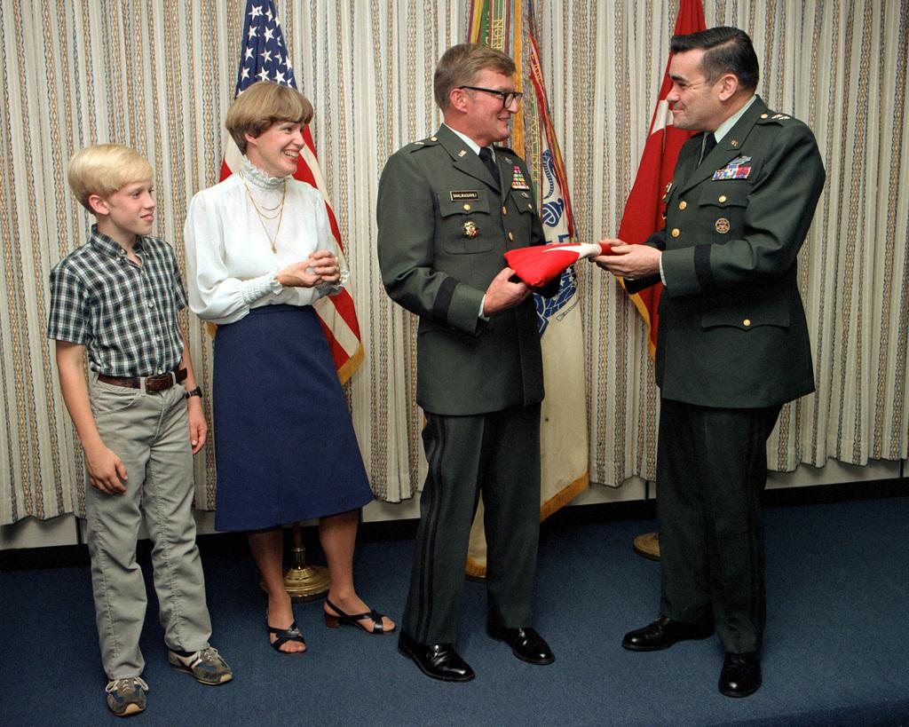 Brig. GEN. John M.D. Shalikashvili receives a flag indicating his new rank of brigadier general from MAJ. GEN. Robert L. Schweitzer, Director of Strategy, Plans and Policy. Brig. GEN. Shalikashvili will become the Deputy Director of Strategy, Plans and Policy. Attending the ceremony at the Pentagon are Brig. GEN. Shalikashvili's wife Joan and son Brant
