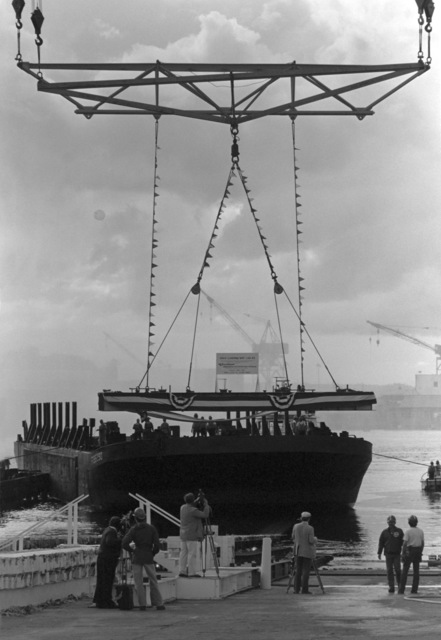"A crane at the Lockheed Shipyard hoists the keel of the dock landing ship (LSD 42) onto a shipyard barge for the ""signing of the keel"" ceremony"
