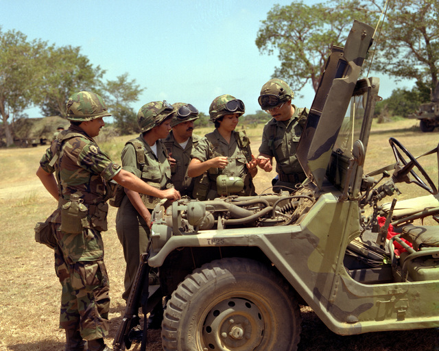 Members of the 432nd Medium Truck Company, 346th Transportation Corps Battalion discuss the procedures for preoperative vehicle maintenance during an annual field training exercise at Camp Santiago. Left to right are SGT. 1ST Class Santos, SPEC. 4 Vinares, 1ST SGT Sanchez, PFC. De Jesus and CAPT. Rodriguez