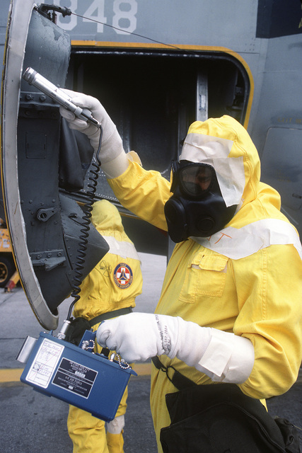 "A member of the Disaster Response Force, wearing a nuclear-biological-chemical (NBC) protective suit, uses a radiacmeters to detect ""radiation contamination"" on an aircraft during Exercise GLOBAL SHIELD at the Strategic Air Command (SAC) headquarters"