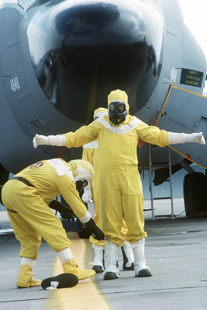 "A member of the Disaster Response Force, wearing a nuclear-biological-chemical (NBC) protective suit, uses a radiacmeter to detect ""radiation contamination"" on another DRF member during Exercise GLOBAL SHIELD at the Strategic Air Command (SAC) headquarters"