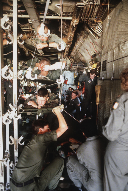 "Air Force medical personnel care for ""casualties"" aboard an Air Force Reserve C-130E Hercules aircraft during Exercise WOUNDED EAGLE '83. The exercise is designed to test the Civilian-Military Contingency Hospital System, a program for transferring wartime casualties to civilian hospitals in the event they overflow military facilities"