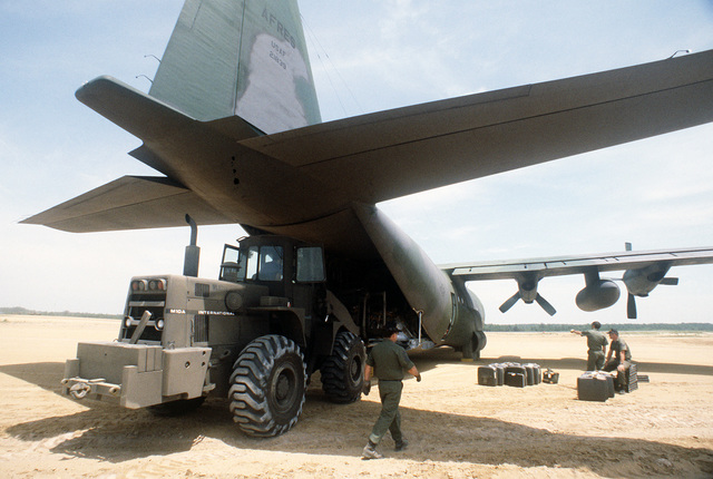 An International M10A terrain forklift is used to unload supplies from an Air Force Reserve C-130E Hercules aircraft during Exercise WOUNDED EAGLE '83. The exercise is designed to test the Civilian-Military Contingency Hospital System, a program for transferring wartime casualties to civilian hospitals in the event they overflow military facilities