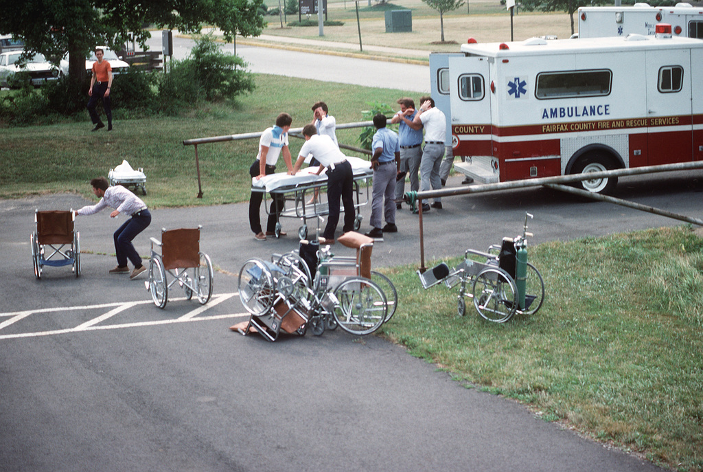 """Civilian medical personnel stand by with a stretcher and wheelchairs as a helicopter carrying """"casualties"""" lands during Exercise WOUNDED EAGLE '83. The exercise is designed to test the Civilian-Military Contingency Hospital System, a program for transferring wartime casualties to civilian hospitals in the event they overflow military facilities"""