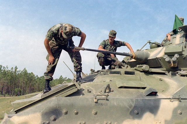 Infantrymen check the gun of an M2 Bradley Infantry Fighting Vehicle prior to firing. The main arament consists of an M242 25 mm Chain Gun