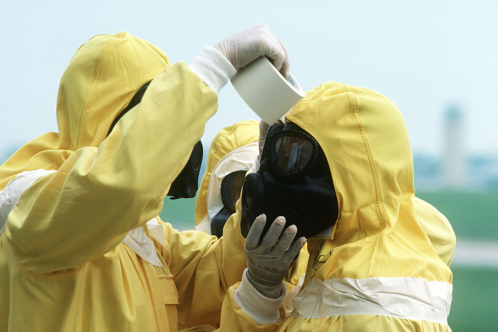 Members of the Disaster Response Force use masking tape to seal any vulnerable areas of their nuclear-biological-chemical (NBC) protective suits as they participate in Exercise GLOBAL SHIELD at the Strategic Air Command (SAC) headquarters