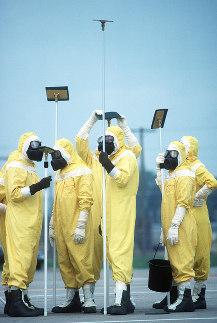 Members of the Disaster Response Force, wearing nuclear-biological-chemical (NBC) protective suits, stand by with decontamination equipment on the flight line during Exercise GLOBAL SHIELD at the Strategic Air Command (SAC) headquarters