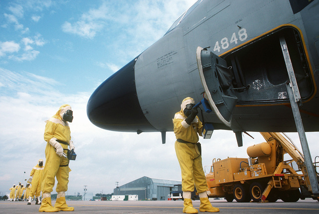 "Members of the Disaster Response Force, wearing nuclear-biological-chemical (NBC) protective suits, use radiacmeters to detect ""radiation contamination"" on an aircraft during Exercise GLOBAL SHIELD at the Strategic Air Command (SAC) headquarters"