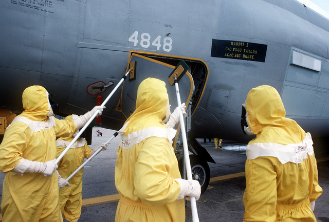 "Members of the Disaster Response Force, wearing nuclear-biological-chemical (NBC) protective suits ""decontaminate"" an aircraft by washing it down during Exercise Global Shield at the Strategic Air Command (SAC) headquarters"