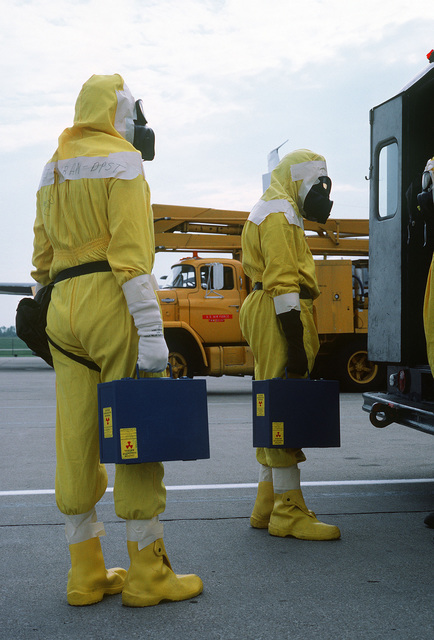 Members of the Disaster Response Force, wearing nuclear-biological-chemical (NBC) protective suits, stand at the back of a van with NBC equipment during Exercise GLOBAL SHIELD at the Strategic Air Command (SAC) headquarters