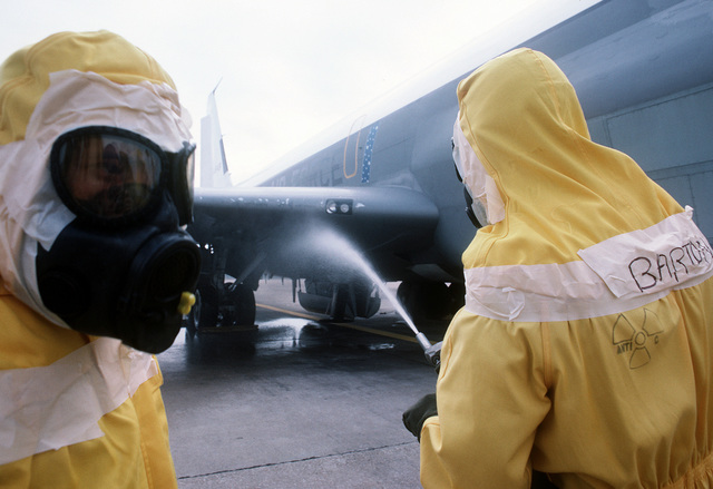 "Members of the Disaster Response Force, wearing nuclear-biological-chemical (NBC) protective suits, ""decontaminate"" an aircraft by washing it down during Exercise Global Shield at the Strategic Air Command (SAC) headquarters"