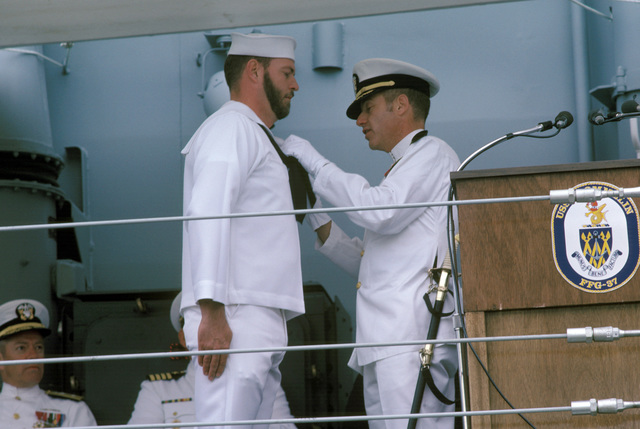 Commander (CDR James W. Orvis, commanding officer, presents a ribbon to a crewman during the commissioning of the Oliver Hazard Perry class guided missile frigate USS CROMMELIN (FFG 37). Seated left, is Commodore (CMDR) Theodore E. Lewin, commander, Naval Base, Seattle
