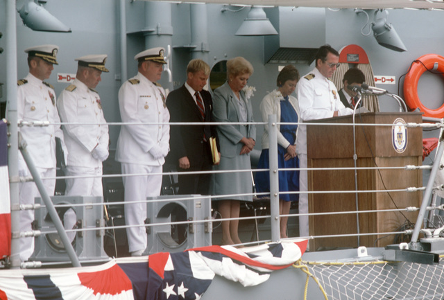 Left to right: Commander (CDR) James W. Orvis, commanding officer; Commodore (CMDR) Theodore E. Lewin, commander, Naval Base Seattle; and Captain (CAPT) Thomas A. Head, commander, Destroyer Squadron Nine, Mrs. Richard B. Meyers, ships sponsor; and John T Gilbride Jr., vice president and general manager of Todd Pacific Shipyard, stand as CAPT Joseph F. Brennan, Chaplain Corps, gives the invocation during the commissioning of the Oliver Hazard Perry class guided missile frigate USS CROMMELIN (FFG 37). (SUBSTANDARD)