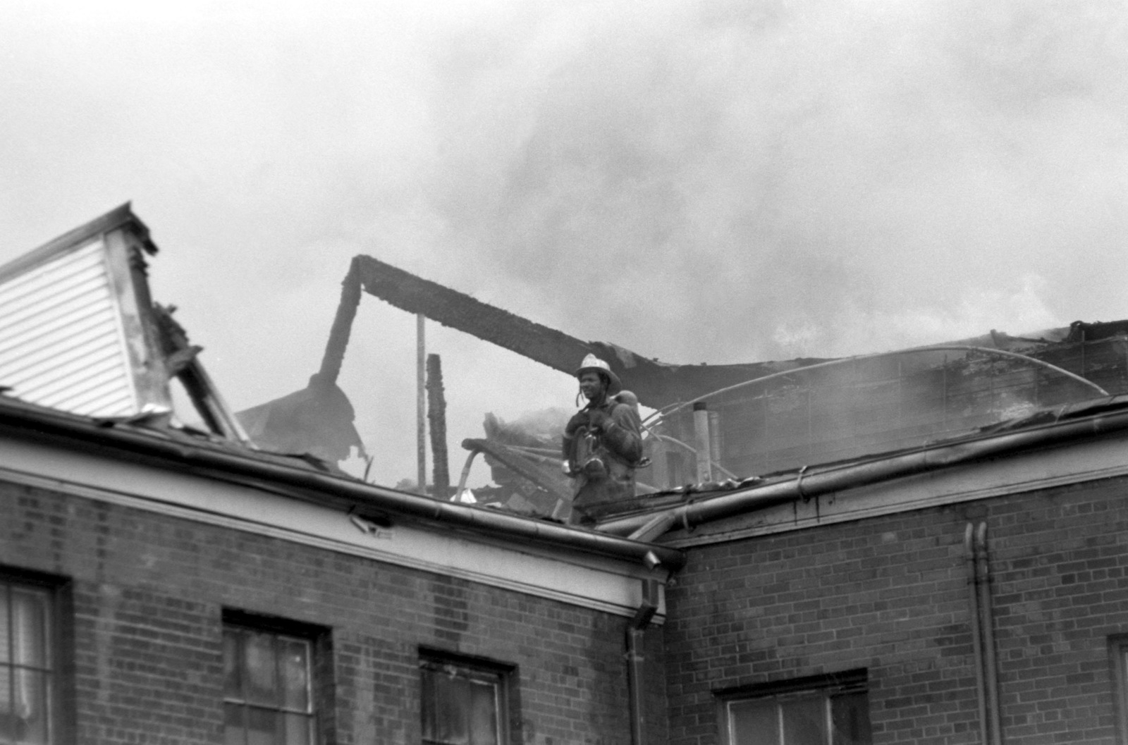 A fire fighter stands on the fire gutted roof of Enterprise Hall at the Anacostia Naval Station, as the District of Columbia and Naval District Washington Fire Departments work to control and extinguish a fire
