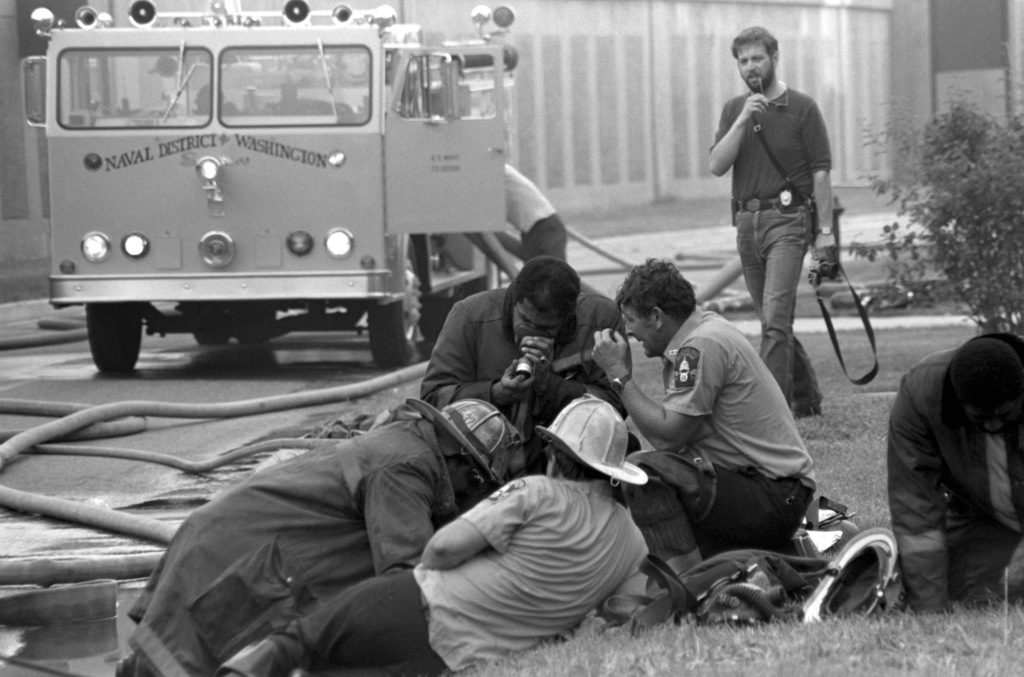 District of Columbia fire fighters breathe from oxygen masks to clear their lungs of smoke, as they work with the Naval District Washington Fire Department to control and extinguish a fire at Enterprise Hall, Anacostia Naval Station