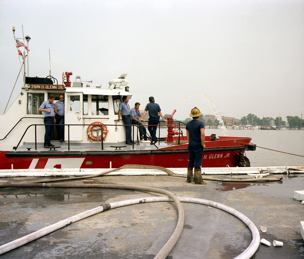 Fire hoses are connected to the District of Columbia fire boat SS JOHN H. GLENN JR. in order to increase water pressure for fire fighters from the District of Columbia and Naval District Washington Fire Departments, as they work to extinguish a fire at Enterprise Hall, Anacostia Naval Station