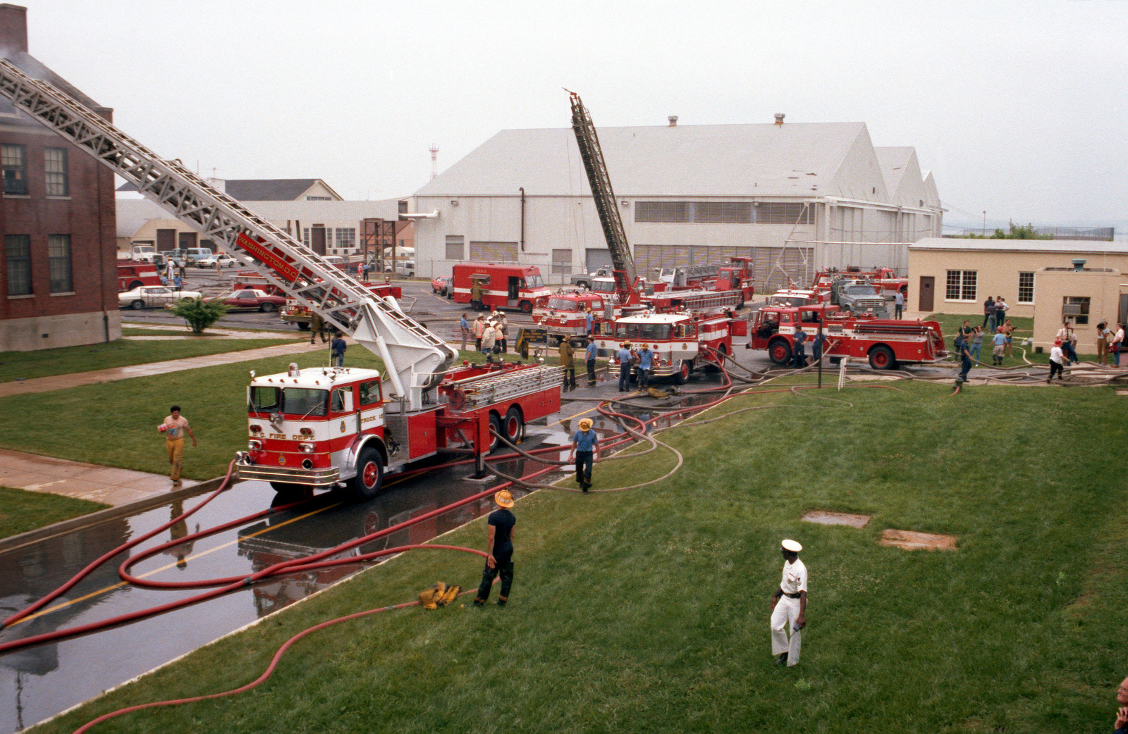 Several fire trucks from the District of Columbia Fire Department are used to assist the Naval District Washington Fire Department in controlling and extinguishing a fire at Enterprise Hall, Anacostia Naval Station