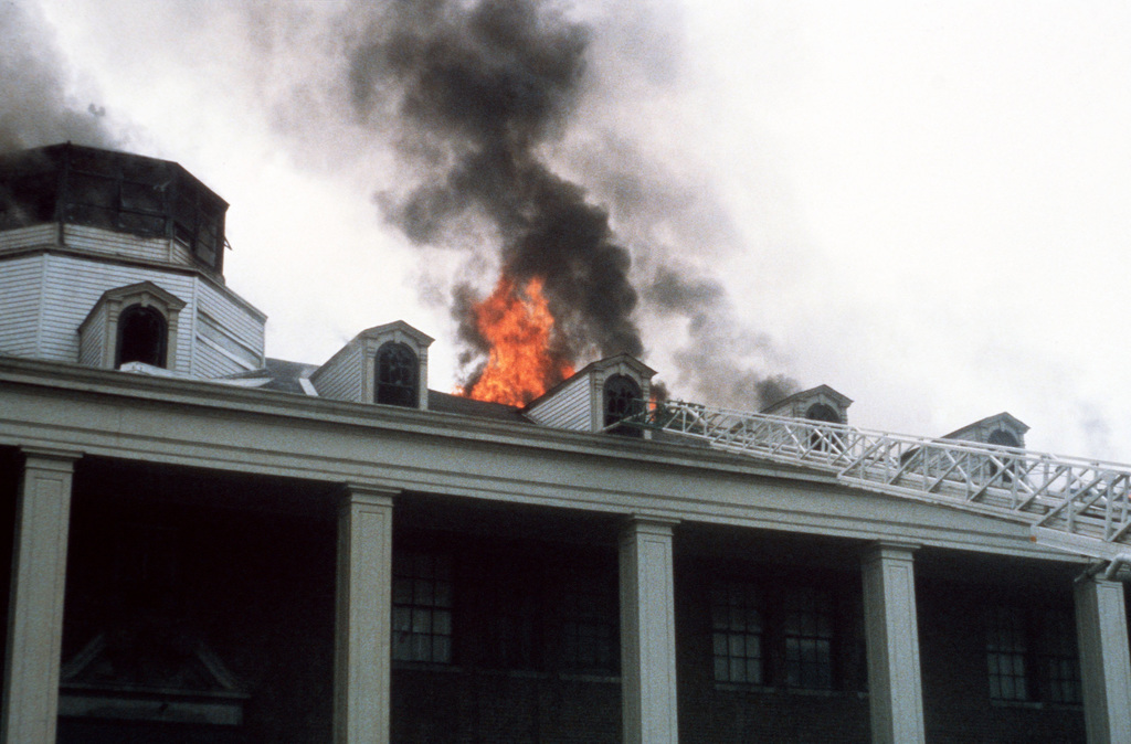 The ladder of a hook and ladder truck is extended onto the back roof of Enterprise Hall at the Anacostia Naval Station, as the District of Columbia and Naval District Washington Fire Departments work to control and extinguish a fire