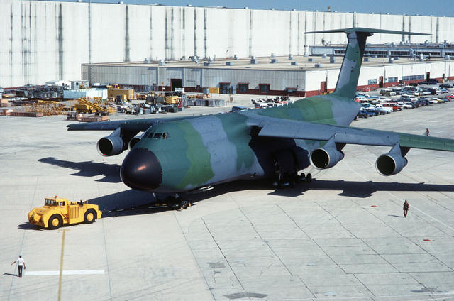 The first camouflaged C-5 Galaxy aircraft is towed out to the flight line at the Air Logistics Center
