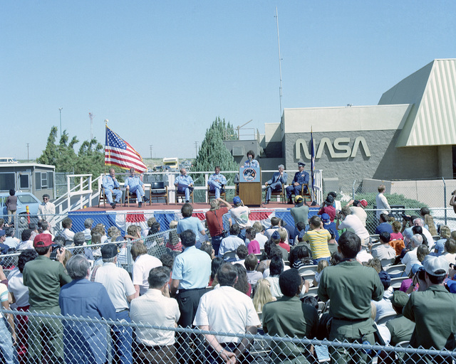 Mission Specialist Dr. Sally Ride, the first American woman astronaut to fly in space, speaks to well-wishers upon her return from space after completing Space Transportation System Mission 7 (STS-7). With her on the platform are, from left to right, Mission Specialists Dr. Norman Thagard and John Fabian; Frederick Hauck, pilot and Robert Crippen, commander