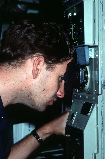 A crewman uses a navigational scope to check bearings aboard the Los Angeles class nuclear-powered attack submarine USS LA JOLLA (SSN-701)
