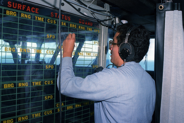 A crewmember makes notations on a surface status board on the bridge of the aircraft carrier USS KITTY HAWK (CV 63)