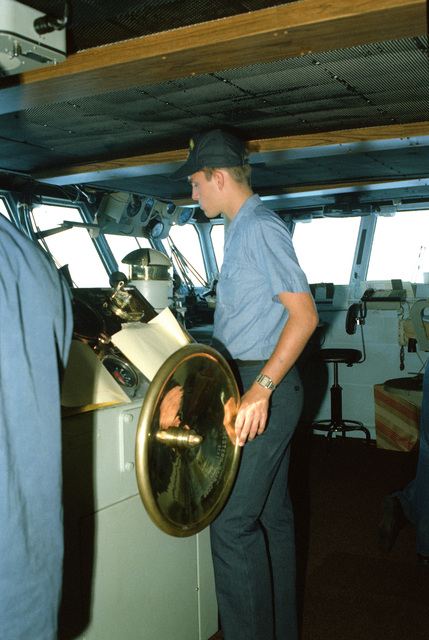 A crewmember mans the helm of the aircraft carrier USS KITTY HAWK (CV 63)