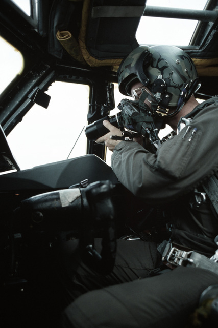 First Lieutenant Kevin Reilly photographs a target ship from the co-pilot's seat inside a B-52 Stratofortress aircraft during a reconnaissance mission. The B-52's are being used to assist the Navy in spotting Soviet ships