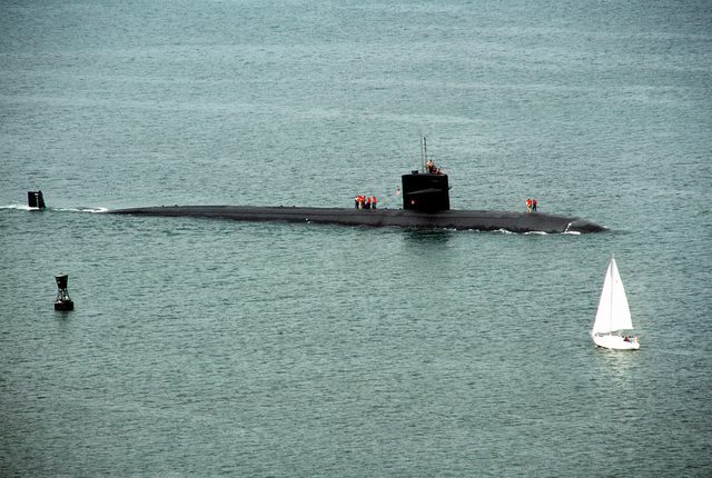 Starboard beam view of the Los Angeles Class nuclear-powered attack submarine USS LA JOLLA (SSN-701) being guided by channel markers to the open sea as she leaves port