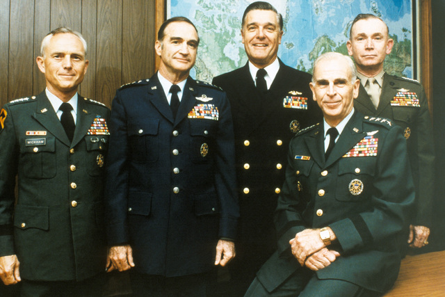 The Joint Chiefs of STAFF (JCS) pose for a protrait in an office at the Pentagon. Standing, from left to right are Army CHIEF of STAFF General (GEN) John A. Wickham, Air Force CHIEF of STAFF GEN Charles A. Gabriel, CHIEF of Naval Operations Admiral James D. Watkins, Commandant of the Marine Corps GEN Paul X. Kelley, and seated to the right, JCS Chairman GEN John W. Vessey. (Substandard image)