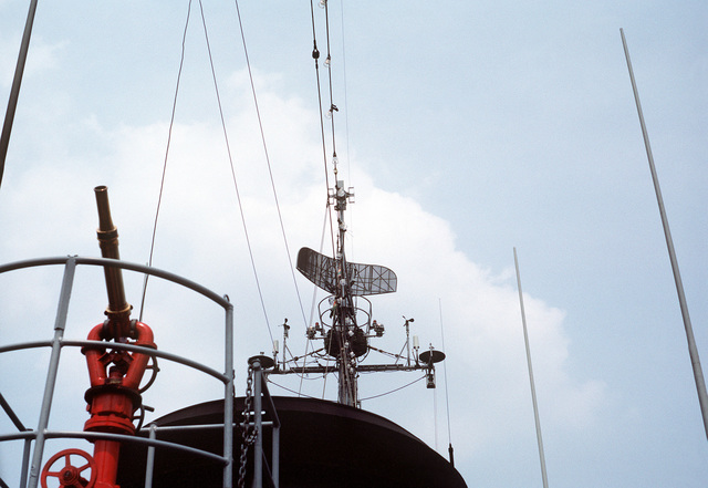 A view of the SPS-7 radar antenna aboard the salvage ship USS HOIST (ARS-40). On the left is one of the high pressure fire fighting nozzles carried by all rescue and salvage ships
