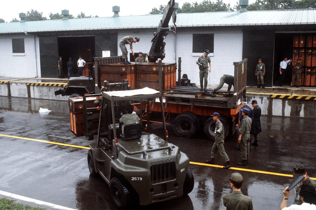 Korean troops use a forklift and a truck to remove crates of 30mm munitions from an open flatrack container. The container, shipped to South Korea from the Seneca Army Depot, California, is being tested by the Air Force as an alternative to the military owned demountable container (MILVAN)