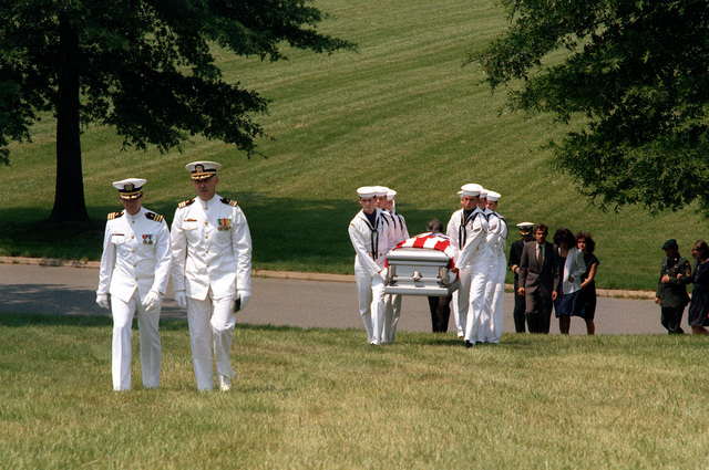Chaplain W.L. Dike, right, leads the Navy Ceremonial Guard as they carry the coffin of LT. CMDR. James T. Ruffin to the burial site at Arlington National Cemetery. Ruffin was listed as missing-in-action after failing to return from flying a mission off the coast of North Vietnam on Feb. 18, 1966