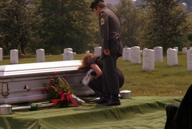 Mrs. T. Bates III is comforted by her husband as she kneels next to the coffin of her brother, LCDR James T. Ruffin, during funeral services at Arlington National Cemetery. Ruffin was listed as missing-in-action after failing to return from flying a mission off the coast of North Vietnam on Feb. 18, 1966