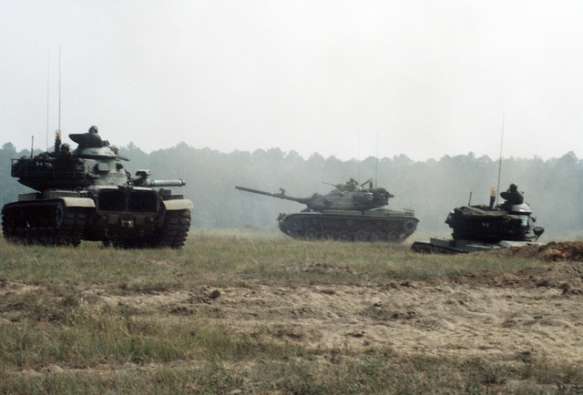 """Three M-60A3 main battle tanks of the 1ST Bn., 108th Armor, 48th Bde., Georgia National Guard, equipped with MILES (Multiple Integrated Laser Engagement System) gear, move out to attack """"enemy"""" positions during a training exercise. The unit is preparing i"""