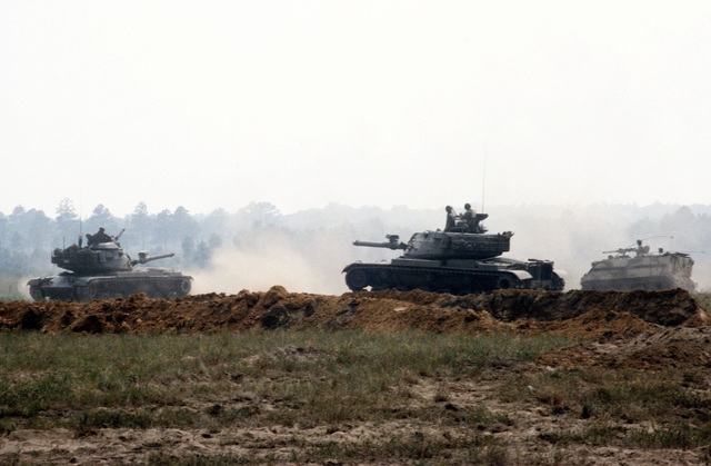 """Two M-60A3 main battle tanks and an M-113 armored personnel carrier of the 1ST Battalion, 108th Armor, 48th Brigade, Georgia National Guard, move out to attack """"enemy"""" positions during an exercise. The unit is preparing for its annual training exercises to be held this year at Fort Irwin, California"""