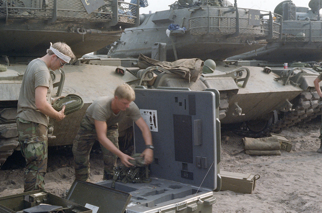 First Lieutenant (1LT) Rick Addison (left) and SPECIALIST 5 (SPC5) Joe Yother (right), 1ST Platoon, 48th Brigade, 108th Armored Division, Georgia National Guard, store equipment in a carrier. The equipment was removed from the M603 main battle tanks (background) used during the training Exercise COMPANY TEAM DEFENSE