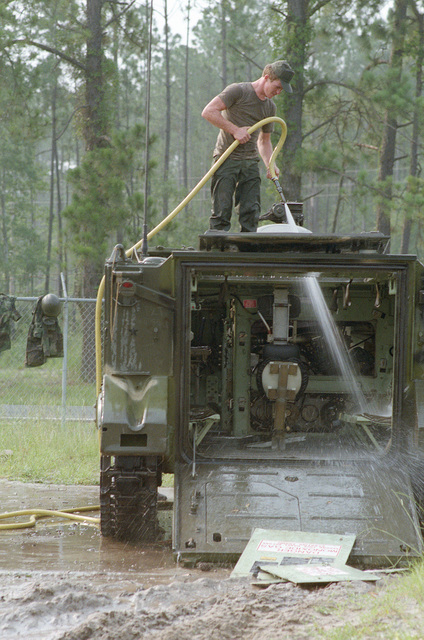 Private First Class (PFC) Richard Strickland, 1ST Platoon, 48th Brigade, 108th Armored Division, Georgia National Guard, washes an M113 armored personnel carrier in the motor pool after the training Exercise COMPANY TEAM DEFENSE