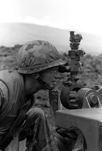 Colonel Radcliff, left, Commanding Officer of the 3rd Marine Regiment, 1ST Marine Brigade, looks through the sight of an M101 105 mm howitzer during Operation ZULU WARRIOR at the Pakalula Training Area