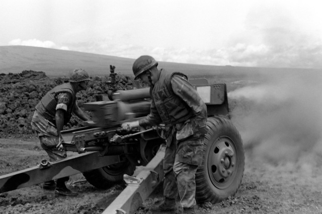 Colonel Radcliff, left, Commanding Officer of the 3rd Marine Regiment, 1ST Marine Brigade, observes as Lieutenant Colonel Roberts, right, Commanding Officer of the 12th Marines, fires an M101 105 mm howitzer during Operation ZULU WARRIOR. The operation is  taking place at the Pakalula Training Area