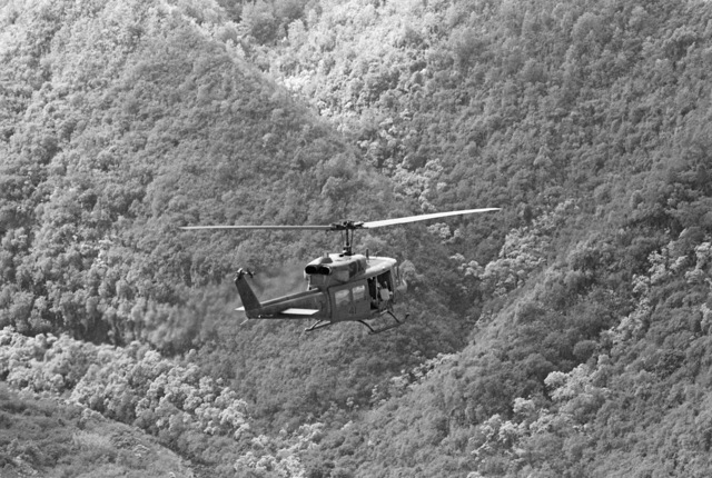 An air-to-air right rear view of a UH-1 Iroquois helicopter from Marine Corps Air Station, Kaneohe Bay, as Marines conduct a composite squadron training exercise