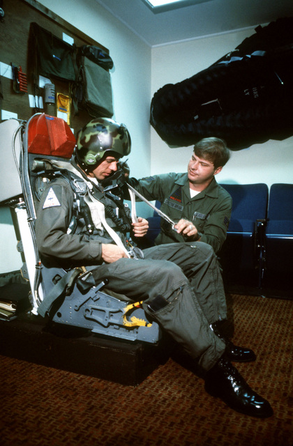 STAFF Sergeant Mark H. Smotherman, a life-support specialist with the 10th Tactical Air Support Squadron, assists Captian Ronald W. Eifert during ejection seat training